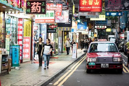Hong Kong,China - April 24, 2018: Hong kong street scenery with crowed people and taxi.