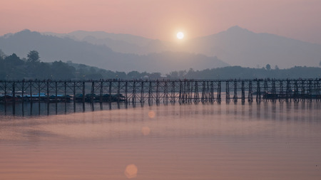 This Wooden Mon Bridge is officially named Uttama Nusorn Bridge with sun light in ter morning. It was built in order to connect with Mon village and Songalia village in Kanchanaburi , Thailand Stock Photo