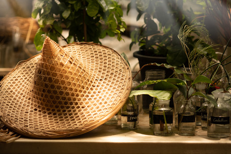 Traditional asian conical bamboo hat on old table with flower in glass bottle and soft light , Vintage image style. Banco de Imagens