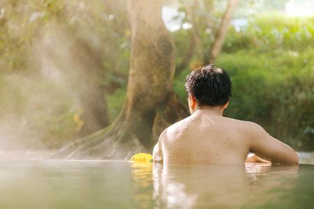 Asian man relaxing in morning is beautiful fog steam hot spring with sunlight  at Hin Dat Hot Spring , Kanchanaburi , Thailand.