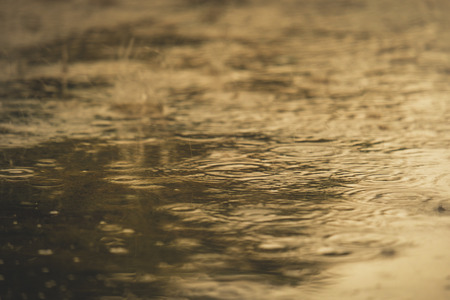 Vintage color tone of close up rain water drop splash falling to the floor in rainy season with Soft sunlight.