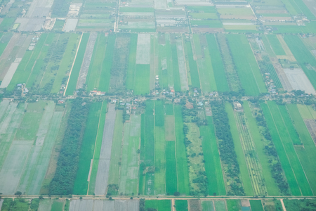 Aerial photo from a plane, top view, field roads and green field and farm in Thailand. Stock Photo
