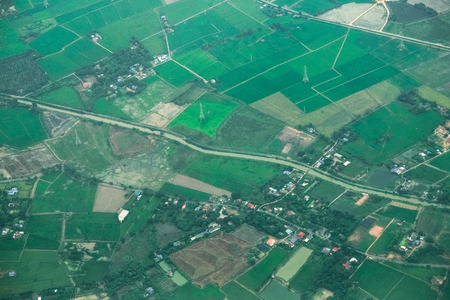 Aerial photo from a plane, top view, field roads and green field and farm in Thailand. 写真素材