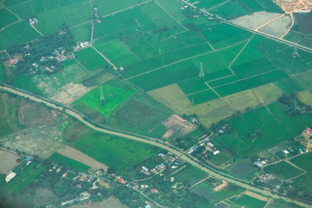 Aerial photo from a plane, top view, field roads and green field and farm in Thailand. Standard-Bild