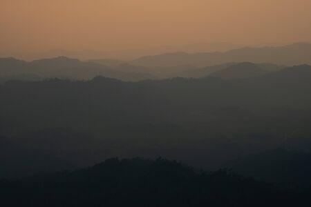 landscape fantastic sunset on foggy autumn forest valley, mystical valley background.