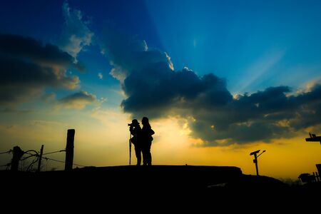 Silhouette of the photographer taking a photo of mountain landscape with sunset, Thailandใ Standard-Bild
