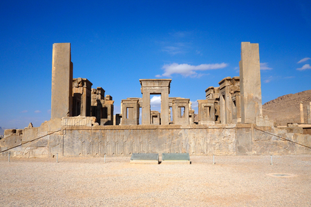 Ruins of Apadana and Tachara Palace behind stairway with bas relief carvings in Persepolis against cloudy blue sky in Shiraz city of Iran. Stock Photo