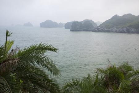 Vietnam, halong, catba. Rocky island in azure sea. Blue cloudless sky. Smaller islands in background Stock Photo