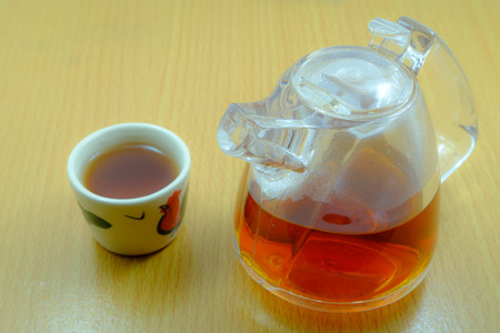 chinese tea cup: Small Chinese teapot and Chinese tea cup on wooden table.