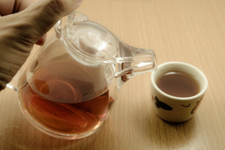 chinese tea cup: Hand on Small Chinese teapot and Chinese tea cup