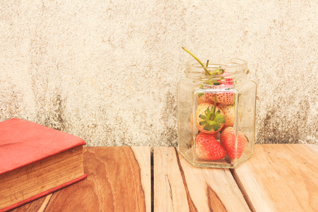 Strawberry jar and a Book on a wooden, process color with Vintage Tones. Focusing on jar. photo