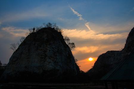 ratchaburi: Contrail in the blue sky and Sunset over Stone mountain, Ratchaburi Thailand. Stock Photo