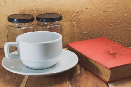 empty jar: White coffee cup, Empty jar and a book on a wooden. Process color with vintage tone.