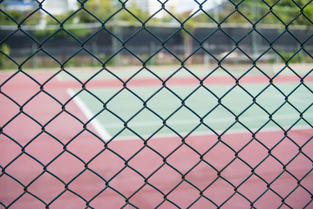 chain link fence: chain link fence and a background of tennis cort, soft fous. Stock Photo