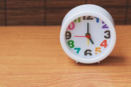 o�??clock: clock on wooden showing 5 oclock Foto de archivo