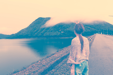 Young Asian girl looking beatiful view of mountains and lake. Retro vintage filter effect. Stock Photo