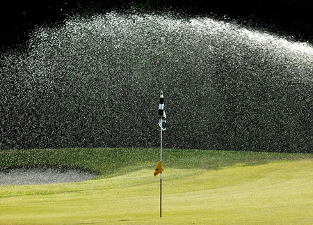 Watering a green on a Golf course in Surrey, England, UK
