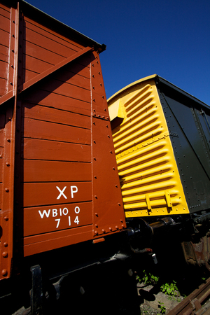 Brightly colored vintage yellow and red train carriages connected to a steam train