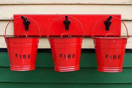 Three red fire buckets mounted on a wall at Pickering Railway Station, North Yorkshire