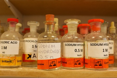 Various bottles of chemicals including Sodium hydroxide in a school chemistry lab