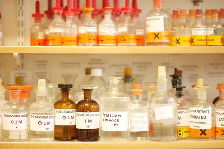 Bottles of chemcicals on shelves in a Science laboratory including Potassium Iodide, Potassium Chloride, Potassium bromide, Sodium nitrate, Chemicals