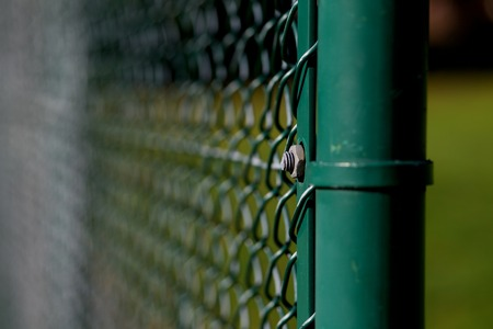 Tennis court mesh with dark green post and out of focus background Stok Fotoğraf - 115374350