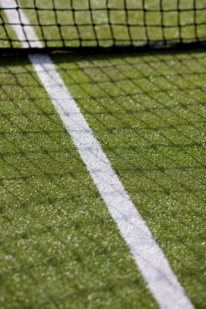 Green tennis court with net and white line marking