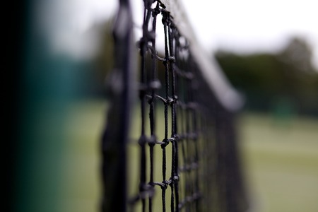 Tennis net on a court with dark green mess and out of focus background