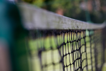 Tennis net on a court with dark green mesh and out of focus background