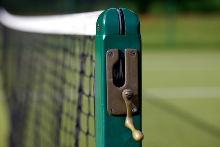 Tennis court net with green post with handle to move net higher or lower.