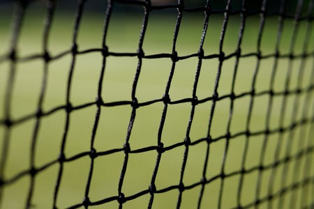 Close up of tennis net with an out of focus green background