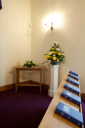 Interior of a Crematorium chapel with flowers, cross, Bibles and candles