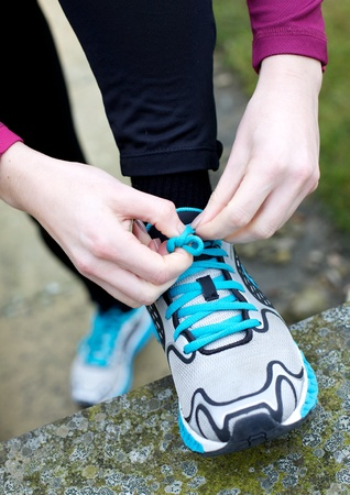 Girl ties her laces in readiness for her running training