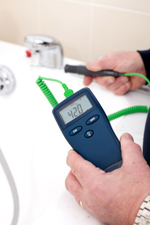 Using a digital thermometer with probe to measure the tempreture of hot tap water