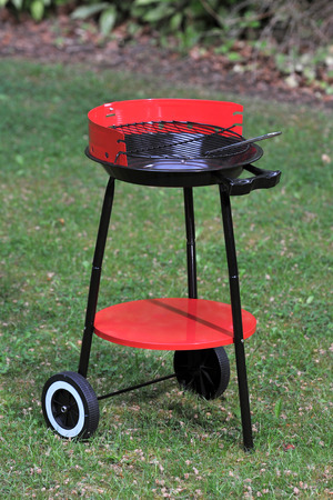 Simple retro red and black foldaway barbeque on wheels Stok Fotoğraf