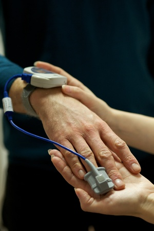 A nurse uses a pulse oximeter to monitor a patients oxygen saturation