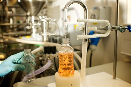 Close up of a Lab technician using an industrial carbonator machine with an orange sugar drink Stok Fotoğraf