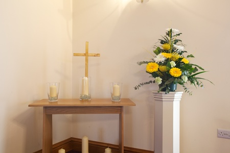 Interior of a Crematorium chapel with flowers, cross and candles Stok Fotoğraf