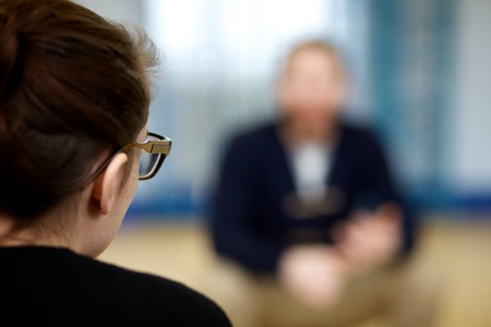 Over the shoulder profile of a girl in glasses getting counselling over mental health issues.