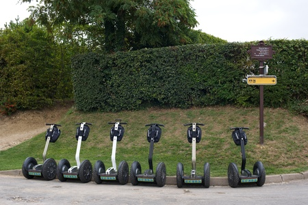 Six segways parked up in a line on the curb in France Editöryel