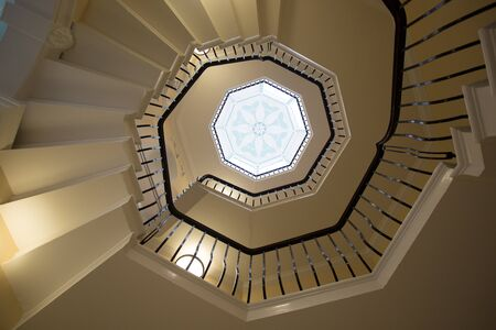 View from the bottom of a spiral staircase looking up to the centre point in the roof of an art deco window, Foto de archivo