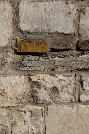 Stone wall with a weathered timber layer amongst the masonry bricks,