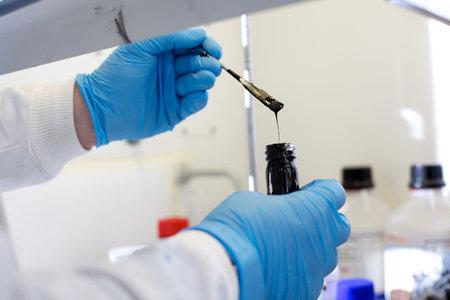 Bio chemistry technician testing material in a fume cupboard
