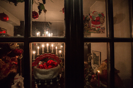 Window with Christmas red and gold decorations and candles in the evening Stock Photo