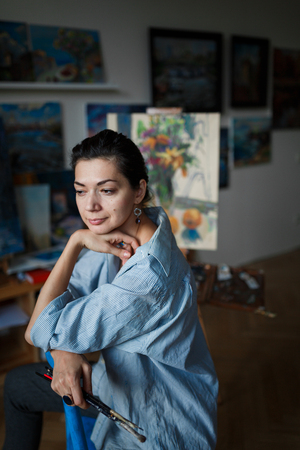 A young smiling brunette woman artist in her studio is holding a brush. Near her easel, paintings and various art equipment. Stok Fotoğraf