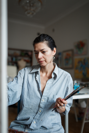A young woman artist sits in a bright studio on a blue chair and paints a picture in oil on the easel. The woman loose comfortable casual clothing. Vertical photo. Stock fotó