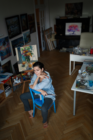 A young smiling brunette woman artist in her studio is holding a brush. Near her easel, paintings and various art equipment. Stockfoto