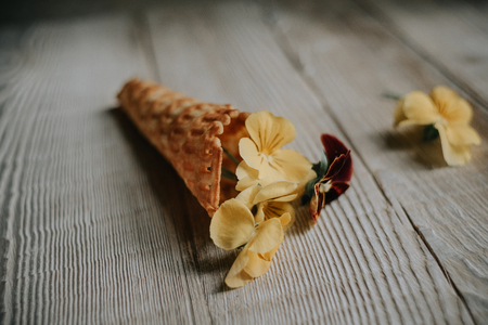 Waffle cones with bouquets of spring flowers and green herbs inside on a wooden rustic background. Soft selective lens focus.