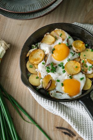 Fried eggs with fried potatoes, green onions on a cast iron pan Stock Photo