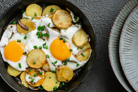 Breakfast fried eggs with fried potatoes, green onions on a cast iron pan Stock Photo